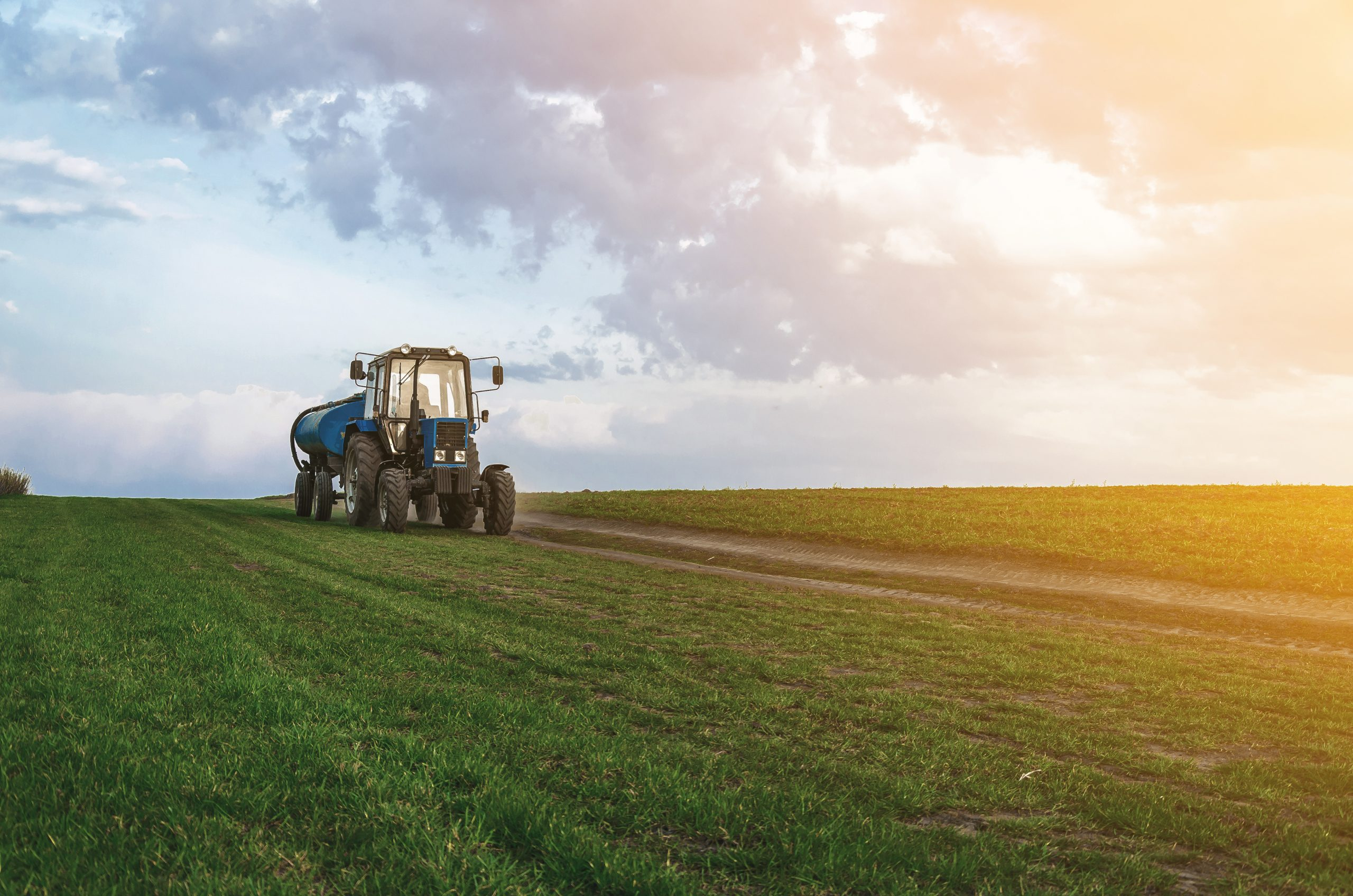 tractor driving on a freshly fertilized agricultural field